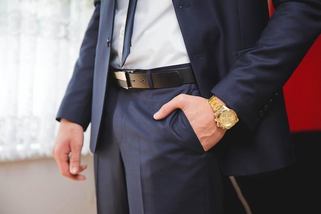 La mano izquierda del novio en su bolsillo