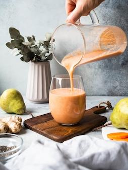 Mano con una jarra de vidrio se vierte en un vaso de zanahoria fresca fresca, pera, licuado de jengibre con semillas de chía