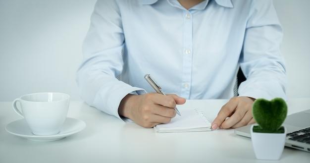 La mano de la joven empresaria asiática toma nota y trabaja en línea desde su oficina en casa, el concepto de enseñanza de distanciamiento social durante las enfermedades por virus covid.