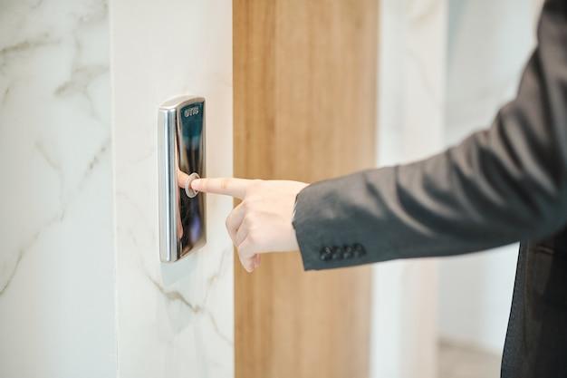 Mano del joven empresario presionando el botón del ascensor mientras está de pie junto a su puerta dentro del hotel o centro de oficinas