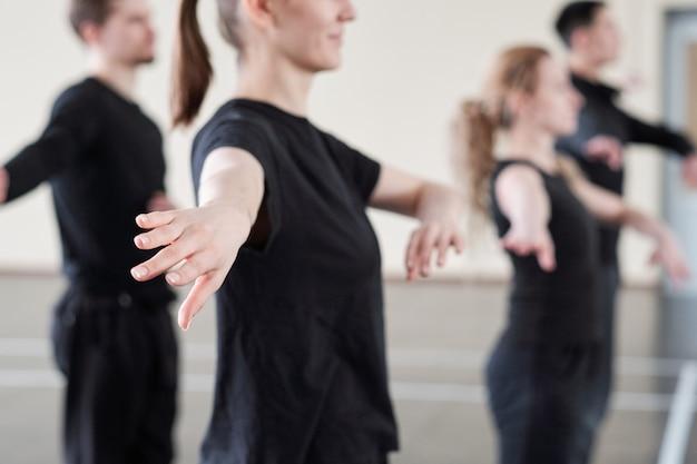 Mano de joven mujer activa en camiseta negra haciendo ejercicio en la lección en el estudio de danza