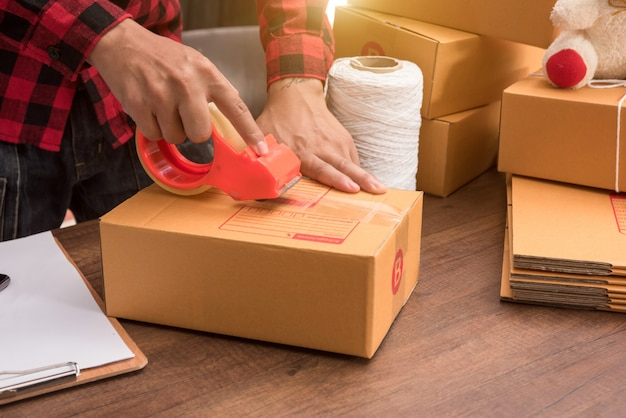 Mano joven mujer preparando paquete para ser enviado en piso de madera