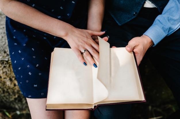 Una mano joven pareja sentada lee un libro abierto sobre las rodillas