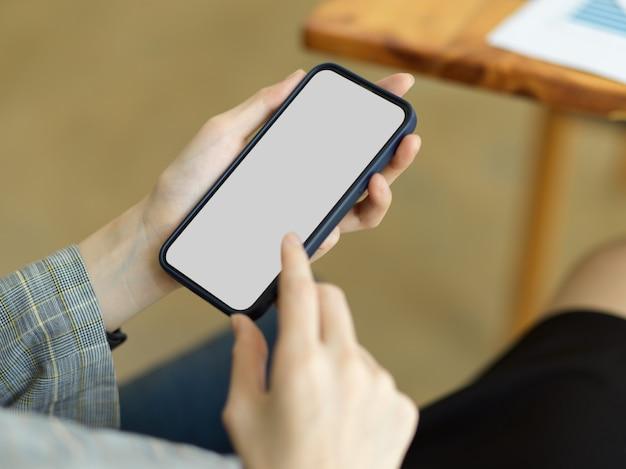 Mano de jovencita sosteniendo teléfono móvil con maqueta de pantalla en blanco ubicada en la oficina