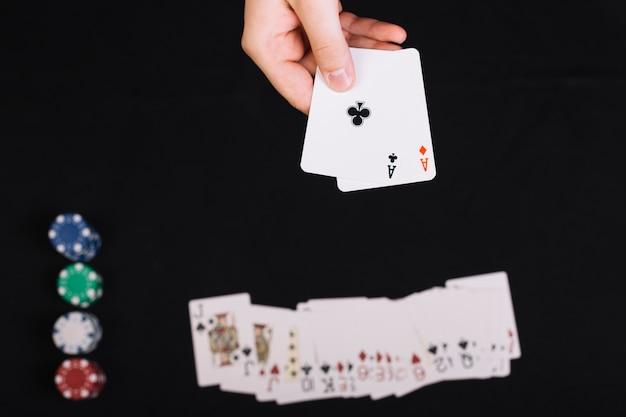 La mano del jugador de póker que sostiene naipes en el contexto negro