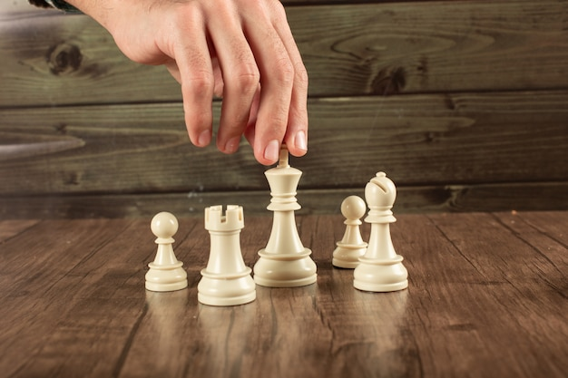 Una mano de jugador tomando rey blanco