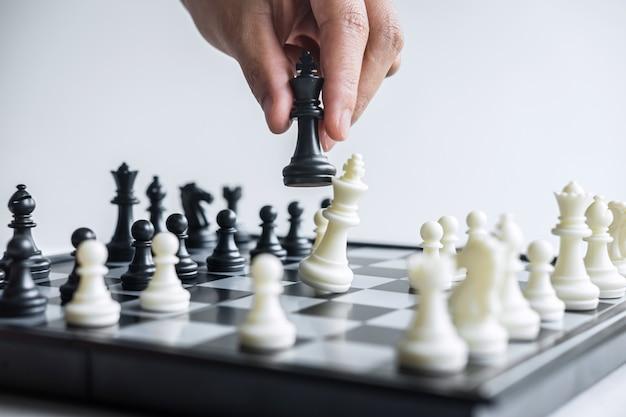 Mano jugando al ajedrez con peones blancos y negros