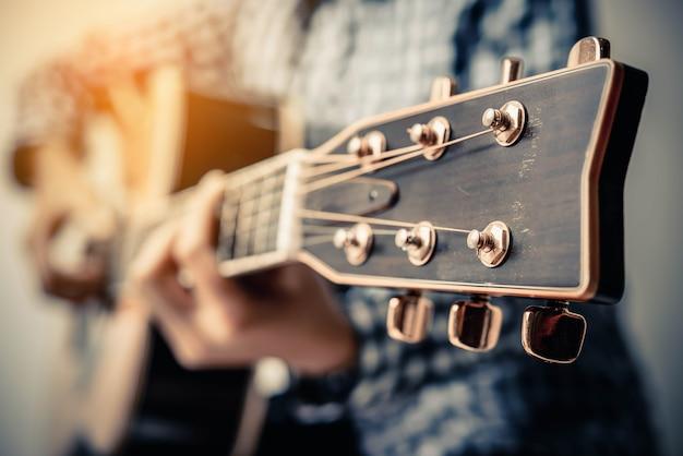 Mano jugar guitarra acústica fingerstyle.
