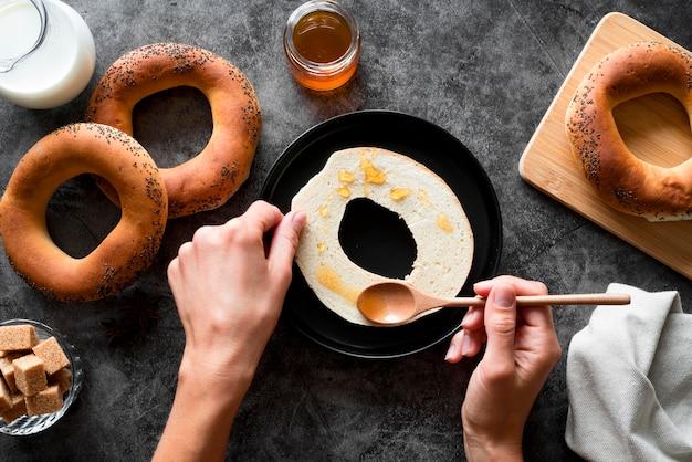 Mano laicos plana extendiendo miel en rodajas de bagel