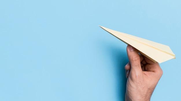 Mano lanzando avión de papel con espacio de copia
