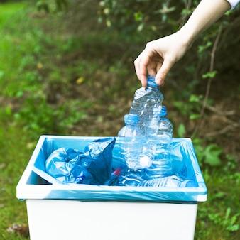 Mano lanzando botella de plástico en la papelera