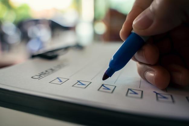 Mano con lápiz azul marcado en la casilla de lista de verificación. de cerca