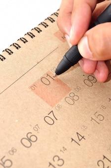 Mano con lápiz tome una nota en el calendario