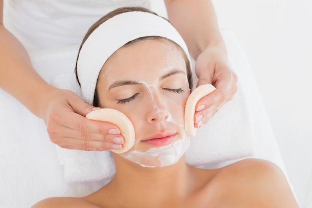 Mano limpiando la cara de mujer con hisopos de algodón en el centro de spa