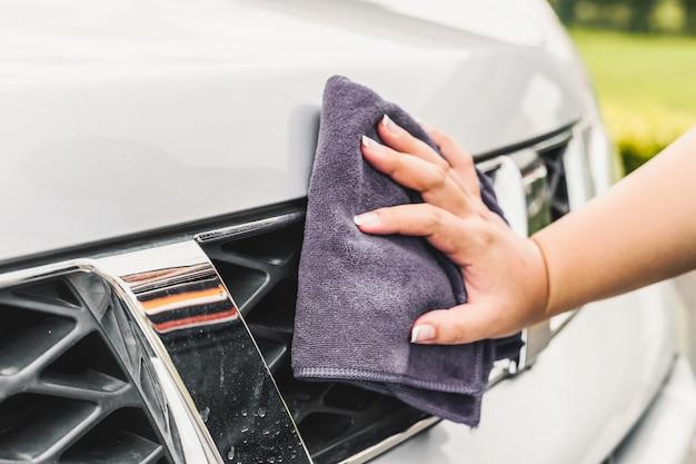 Mano limpiando un coche de cerca
