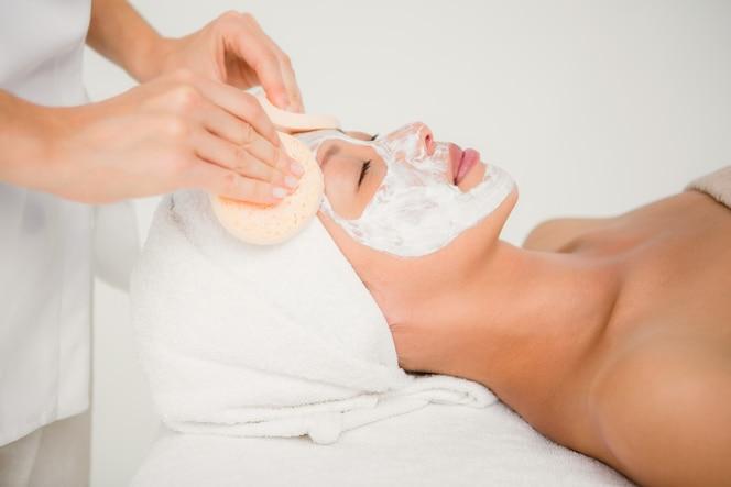 Mano limpiando la cara de mujer con hisopos de algodón