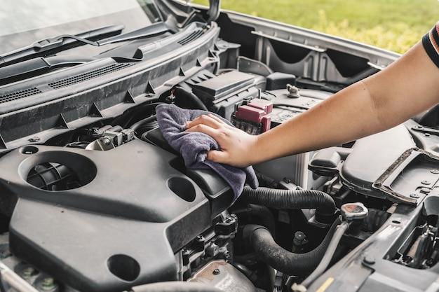 Mano limpiando protector del motor