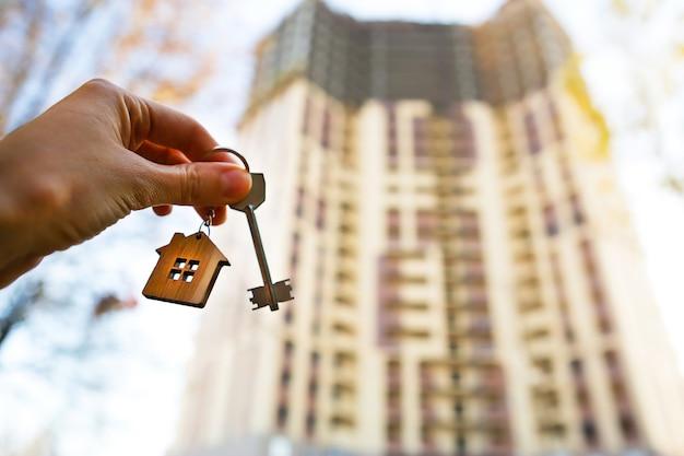 Mano con una llave y un llavero de madera-casa frente a un gran edificio