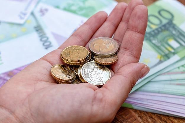 Mano llena de monedas en el dinero