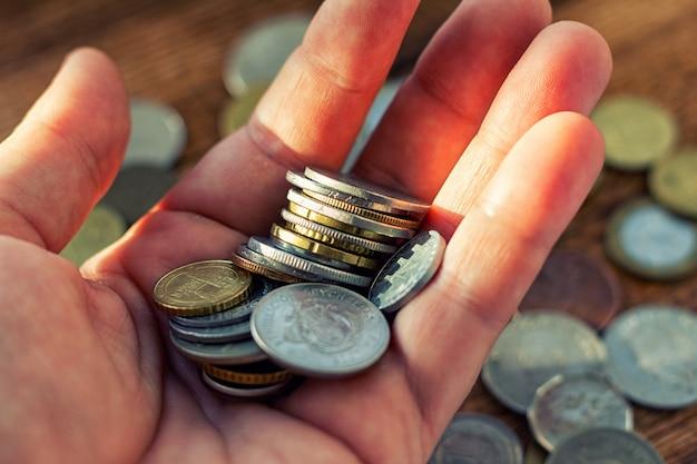 Mano llena de monedas en una palma. concepto de donación de pago.