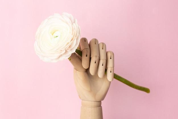 Mano de madera con una flor blanca sobre una rosa
