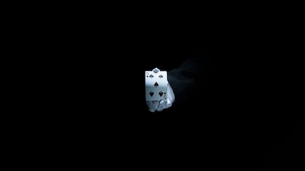 La mano del mago que muestra el naipe del club contra fondo negro