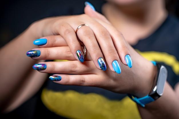 La mano de manicura de brillo de color tiene diferentes manchas en un fondo claro