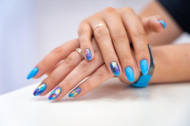 La mano de manicura de brillo de color tiene diferentes manchas en una luz