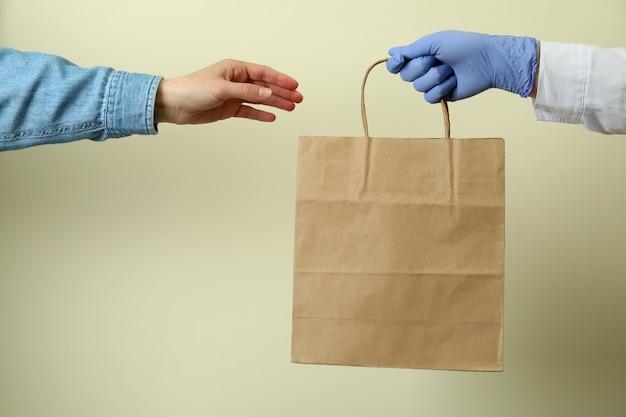Mano a mano dar una bolsa de papel a la mujer