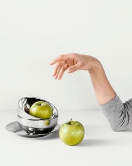 Mano y manzanas de concepto mínimo abstracto