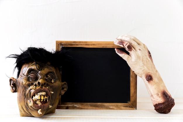 Mano y máscara de monstruo cerca de la pizarra
