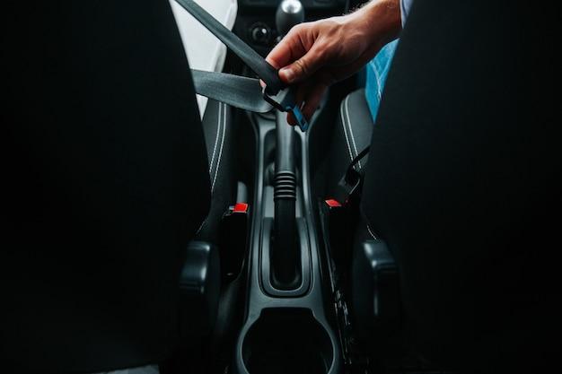 Mano masculina abrocharse el cinturón de seguridad del coche. cierre el cinturón de seguridad del automóvil mientras está sentado dentro del automóvil antes de conducir