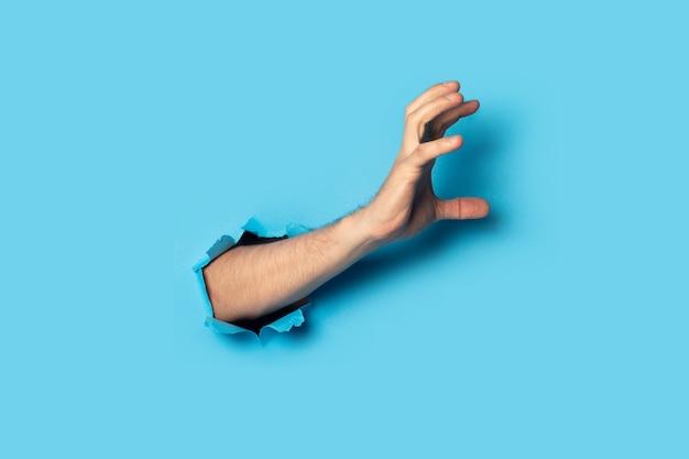 Mano masculina agarra algo en azul