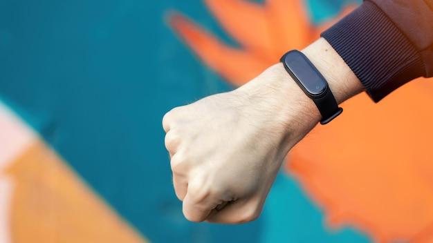 Una mano masculina apretada en un puño con pulsera de fitness, fondo multicolor