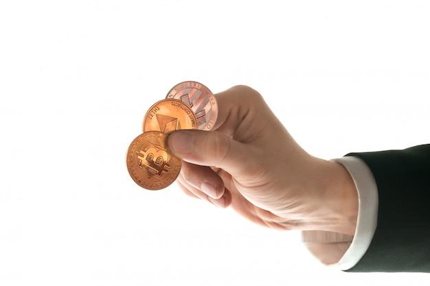 Mano masculina con bitcoin dorado sobre fondo blanco.