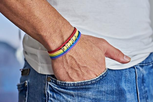 Mano masculina con brazalete de arco iris y orgullo de texto en el bolsillo de los pantalones vaqueros. libertad y concepto lgbt