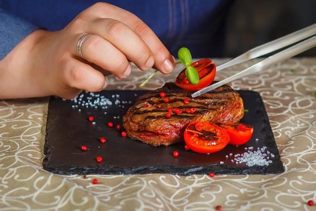 Mano masculina del cocinero que adorna filetes crudos con la especia y la hierba.