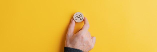 Mano masculina colocando un círculo de corte de madera con símbolo de personas en él