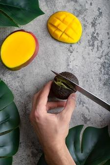 Mano masculina corta aguacate maduro fresco con un cuchillo en la mesa de piedra.