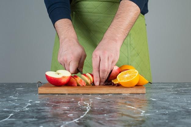 Mano masculina cortando manzana fresca en la parte superior de la tabla de madera en la mesa.