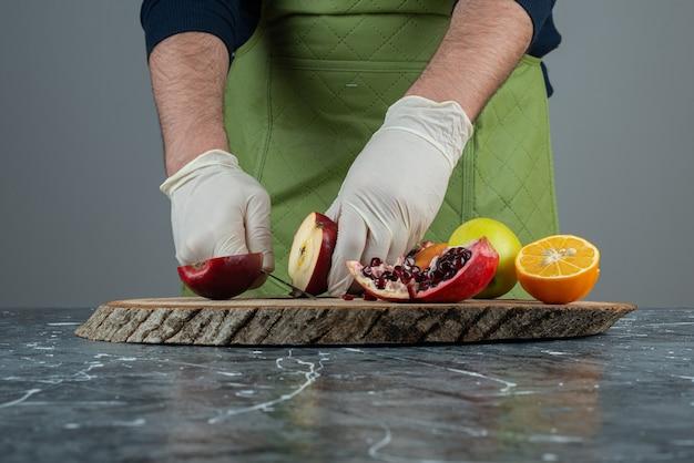 Mano masculina cortando manzana roja en la parte superior de la tabla de madera en la mesa.
