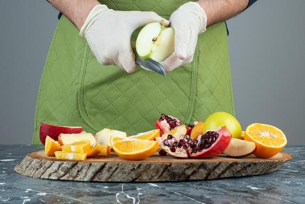 Mano masculina cortando manzana verde en la parte superior de la tabla de madera en la mesa.