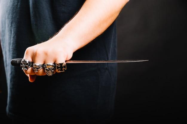 Mano masculina con la daga afilada