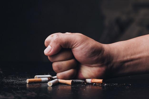 Mano masculina destruyendo cigarrillos sobre fondo negro. deje de fumar. día mundial sin tabaco