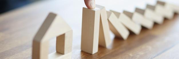 Mano masculina detener la caída de bloques de madera en la casa de juguete closeup