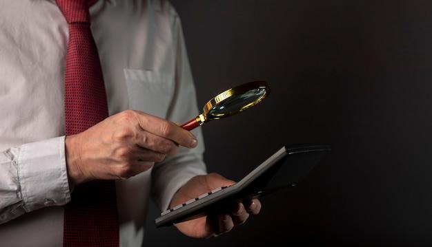 Mano masculina de empresario sosteniendo calculadora y lupa con espacio de copia.