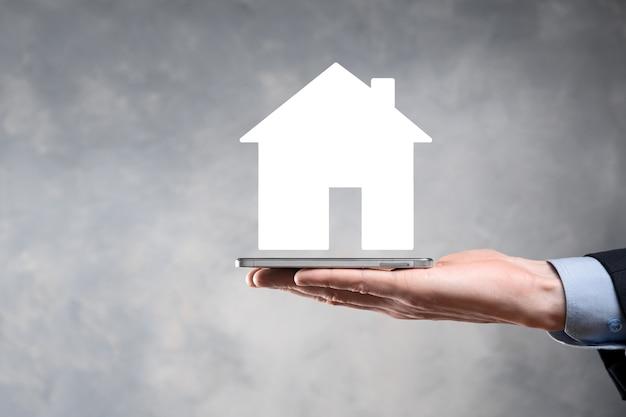 Mano masculina de empresario sosteniendo el icono de la casa en la pared azul. seguro de propiedad y concepto de seguridad concepto de bienes raíces bandera con espacio de copia.