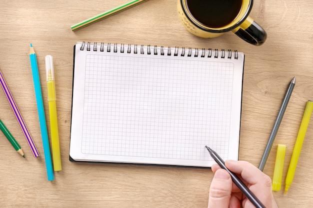 Mano masculina escribe plan de acción o dibuja en cuaderno de espiral