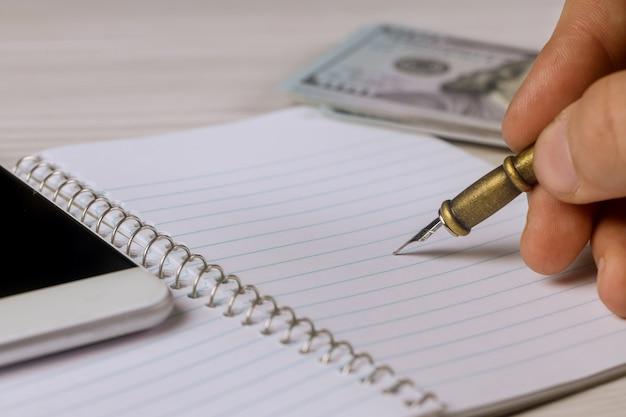 Mano masculina escribe una pluma en el bloc de notas de los dólares, teléfono inteligente
