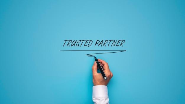 Mano masculina escribiendo un signo de socio de confianza con marcador negro sobre fondo azul.